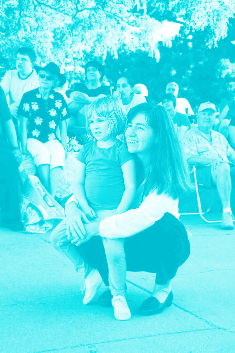 A girl sits on the knee of a woman in the audience as they watch a Jazz in June concert performance