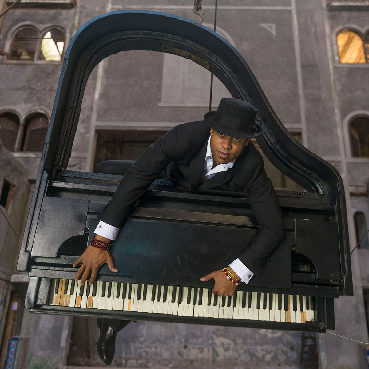 Roberto Fonseca inside a suspended baby grand piano.